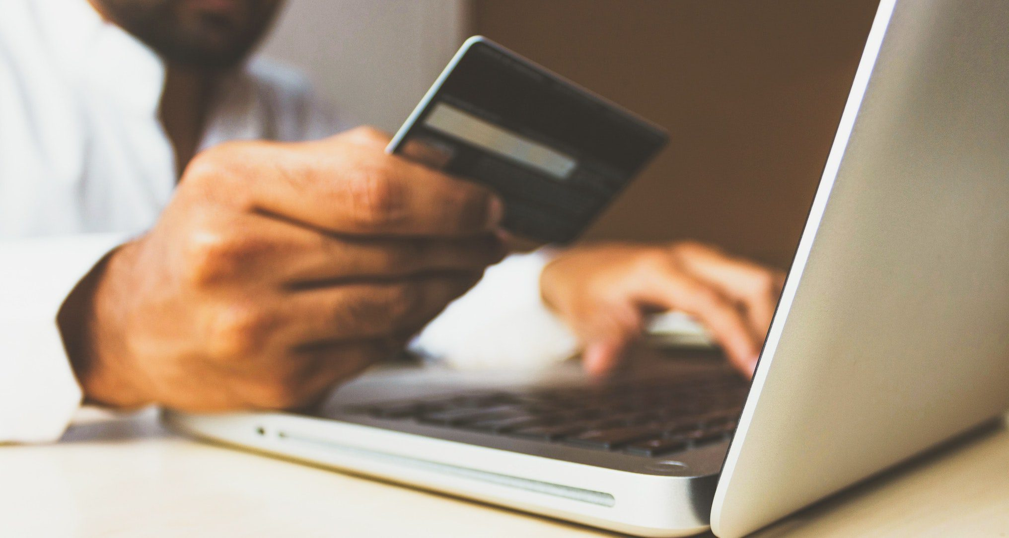 person typing on laptop and holding credit card