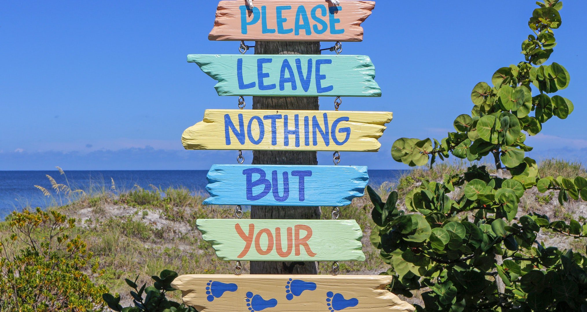 sign on beach saying please left nothing but your footprints