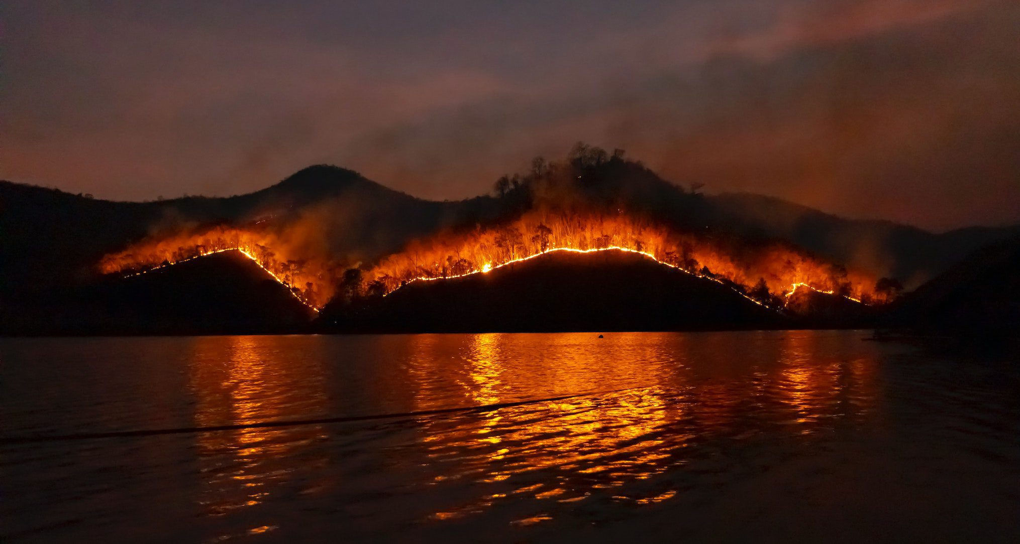 fire on mountains overlooking lake