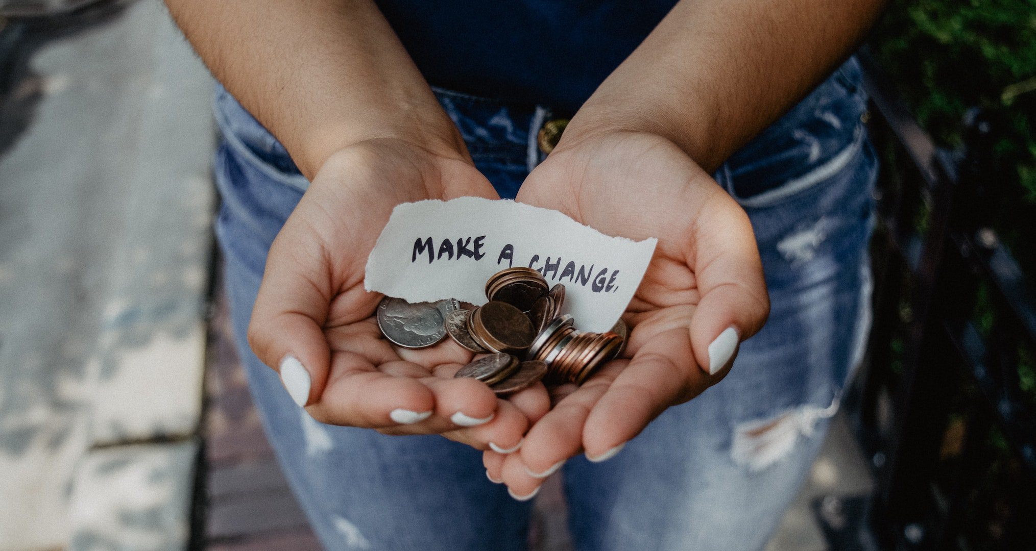 person holding coins with a sign saying make a change