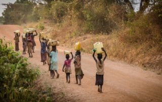 children walking down dirt road carrying jugs of water above their heads