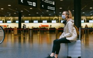 girl wearing a mask sitting on a suitcase inside of an airport