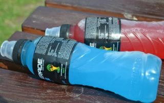 red and blue sports drinks on a picnic table