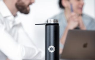 reusable water bottle with man and woman working on a laptop in background