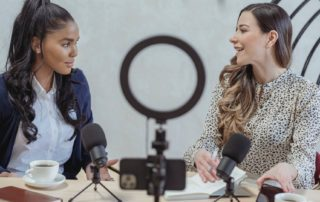 two girls sitting at a table recording a podcast